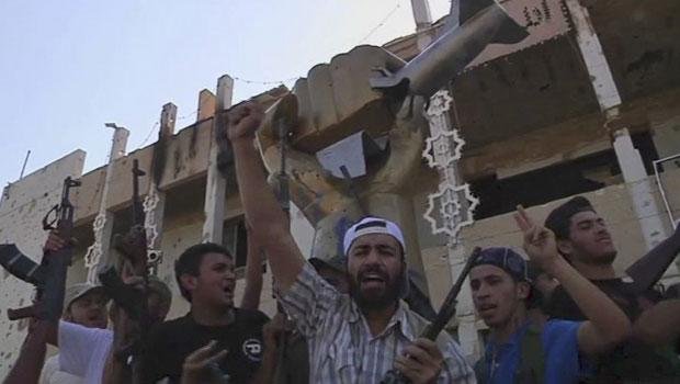 Rebeldes celebram na fortaleza invadida de Muammar Kadhafi em Trípoli, capital da Líbia, nesta quarta-feira (24) (Foto: AP)