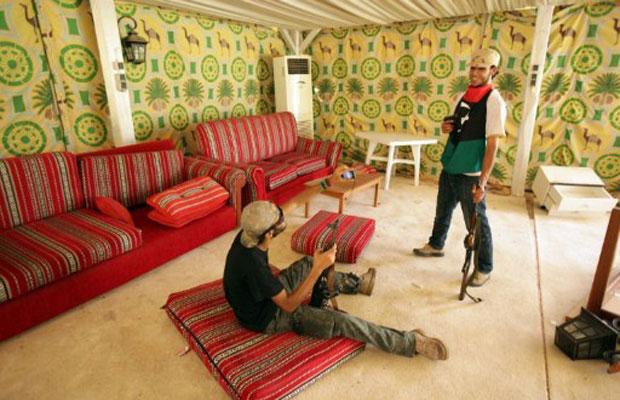 Rebeldes líbios tiram fotos dentro da tenda beduína em que o ditador Muammar Kadhafi costumava receber autoridades estrangeiras, em seu complexo residencial em Trípoli, nesta quarta-feira (24) (Foto: AFP)