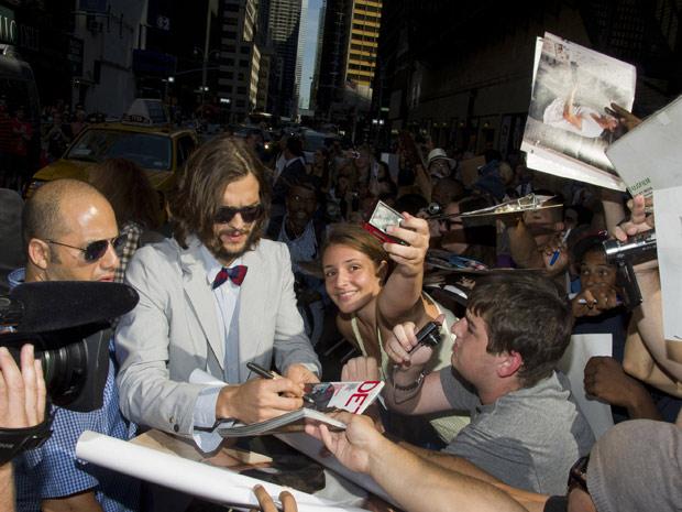 O ator Ashton Kutcher é cercado por fãs antes da gravação do programa de David Letterman (Foto: AP)