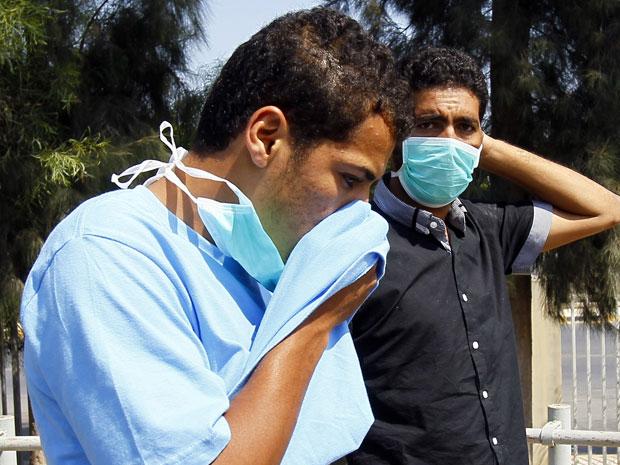Líbios cobrem o rosto para suportar o cheiro próximo ao hospital de Abu Salim, em Trípoli, nesta sexta-feira (26) (Foto: AP)