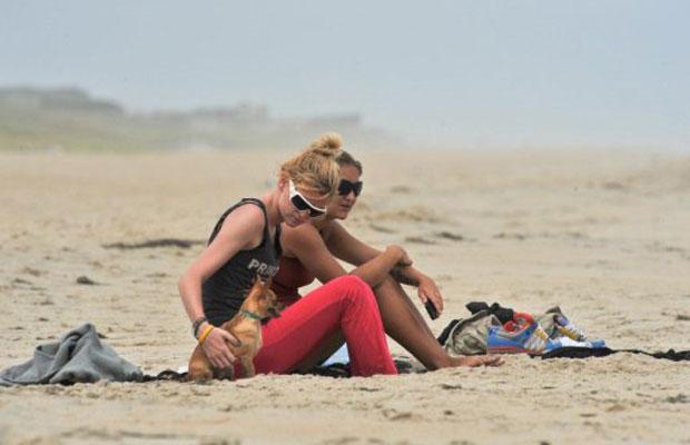 Mulheres e cão nesta sexta-feira (26) na praia de Kill Devil Hills, na Carolina do Norte, praticamente deserta antes da chegada de Irene (Foto: AFP)