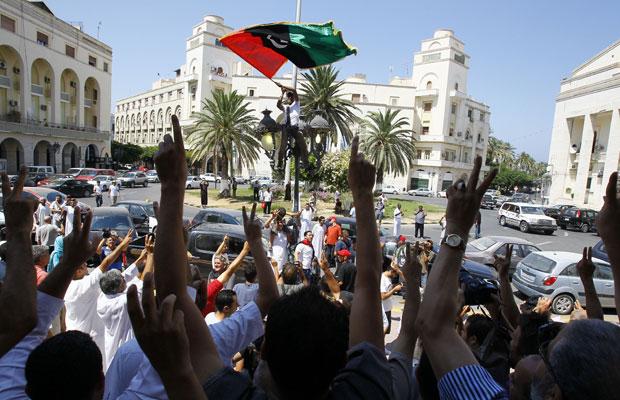 Líbios celebram a queda de Kadhafi nesta sexta-feira (26), após as orações, na região central de Trípoli (Foto: AP)