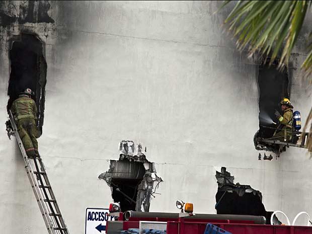 Bombeiros fazem buracos numa parede do cassino para combater as chamas. (Foto: Hans Maximo Musielik / AP Photo)