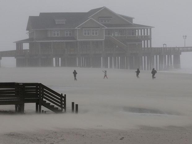 Pessoas caminham por Nags Head, no litoral da Carolina do Norte, mesmo com os efeitos do furacão Irene (Foto: AP)