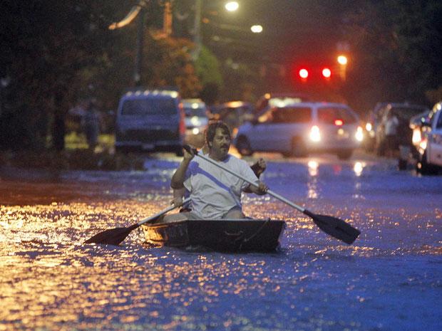 Dois homens usam botem para circular por via alagada na Carolina do Norte durante passagem do furacão Irene pelo estado (Foto: John Bazemore/AP)