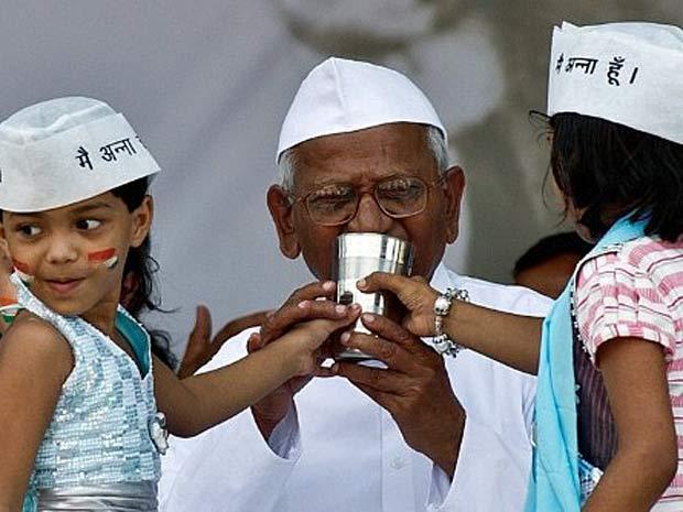 Ativista Anna Hazare quebra jejum ao tomar água de coco com mel, mistura oferecida por duas meninas. (Foto: Manan Vatsyayana / AFP Photo)