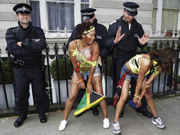 Mulheres dançam para policias no carnaval de Notting Hill em Londres, neste domingo (28) (Foto: Reuters)