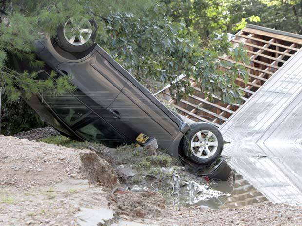 Carro virado durante inundação em Waterbury, no estado americano de Vermont, nesta segunda-feira (29) (Foto: AP)