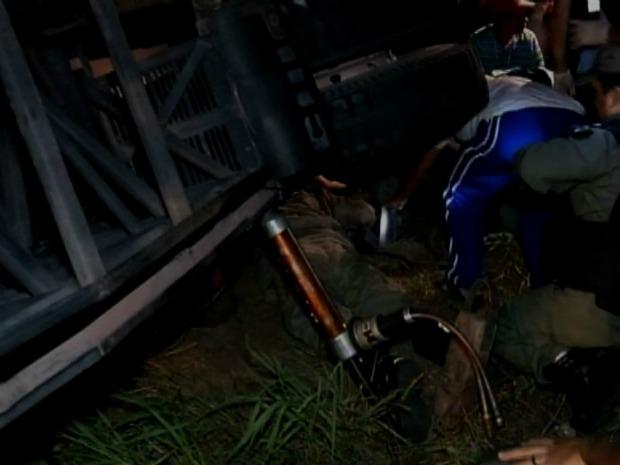 Bombeiro (macacão cinza) entra embaixo do ônibus para retirar vítimas presas nas ferragens. (Foto: TV Verdes Mares/Reprodução)