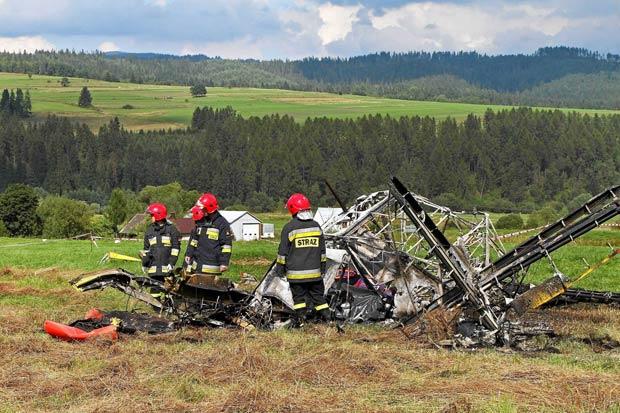 Grupo de bombeiros observa destroços de um avião JAK-12 que caiu em Nowy Targ, sudeste da Polônia, matando o piloto (Foto: Marek Podmokly/ / Reuters)