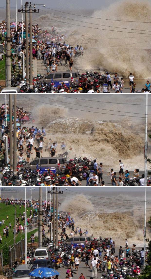Uma multidão de chineses é vista nesta quarta-feira (31) correndo da tromba d'água vinda da represa do rio Qiangtang, em Haning, leste da província chinesa de Zheijang. Moradores e visitantes se reúnem anualmente nesta época no local desde cedo para presenciar as trombas d'água, comuns por conta das fortes chuvas da estação. Não foi divulgado se alguém ficou ferido. (Foto: AFP)