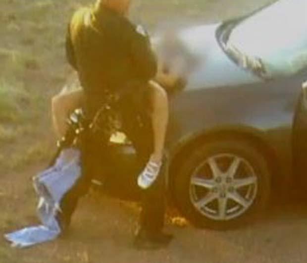 Policial foi flagrado fazendo sexo em serviço sobre o capô do carro patrulha. (Foto: Reprodução)