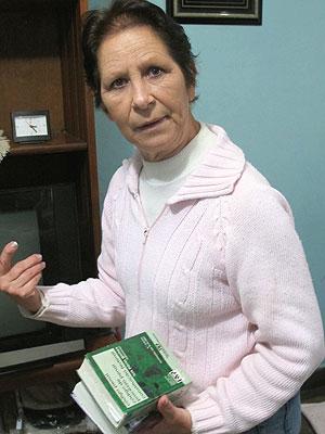 Valquíria mostra o Código Penal e a Constituição Federal: ela passou a estudar a legislação na tentativa de condenar os assassinos do filho (Foto: Raphael Prado/G1)