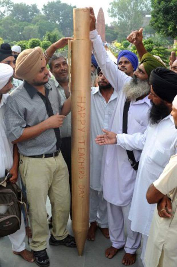 Amritpal Singh (esq) com a caneta de 2,13 metros. (Foto: Narinder Nanu/AFP)