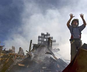 Bombeiro acena para colegas durante trabalho nos escombros do WTC, em 11/9 (Foto: The New York Times)