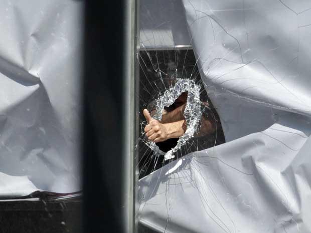 Homem fez gestos após quebrar o vidro de uma janela. (Foto: Daniel Munoz / Reuters)