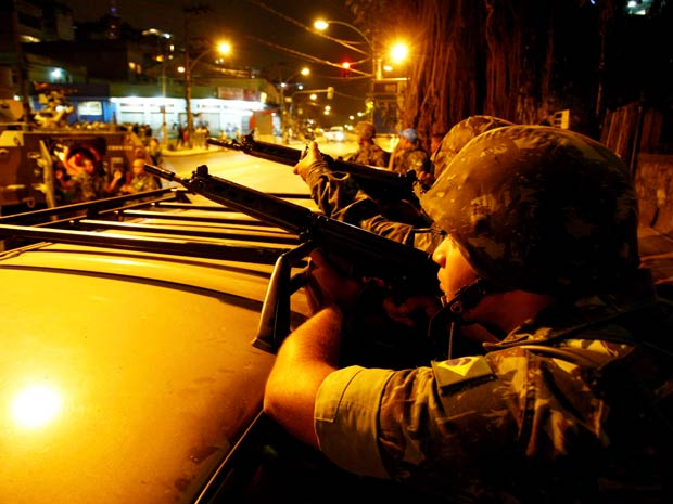 Militares tracam tiros no Complexo do Alemão. (Foto: Pablo Jacob / Agência O Globo)
