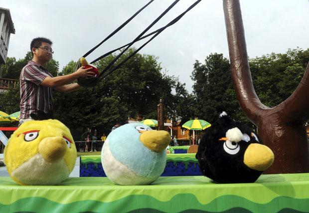 """O objetivo do game é mantido na versão """"real"""". No parque, contudo, os jogadores usam um estilingue gigante e devem fazer força, ou pedir a ajuda de amigos, para conseguir lançar os pássaros em versão de pelúcia contra os obstáculos. Dependendo da forma como as paredes são derrubadas, os porcos verdes feitos de balões estouram, dando prêmios para os jogadores. (Foto: China Daily/Reuters)"""