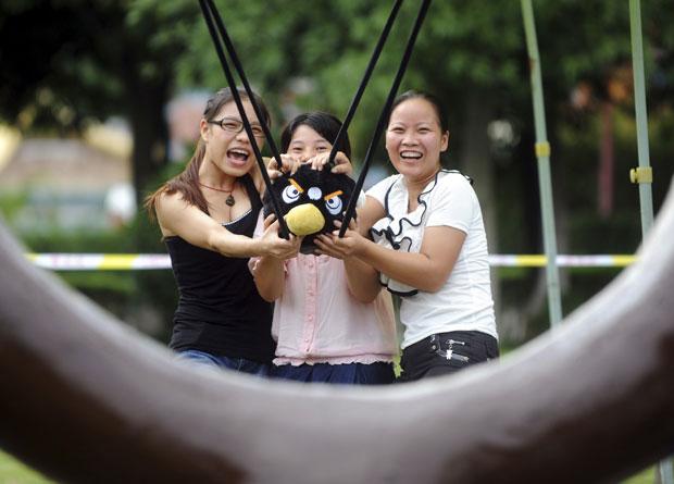 """Um parque de diversões na China criou uma versão real do game """"Angry Birds"""", sucesso nas plataformas móveis como iPhone e celulares com Android, em consoles e no PC, em que os jogadores devem lançar os pássaros para eliminar os porcos verdes. (Foto: China Daily/Reuters)"""