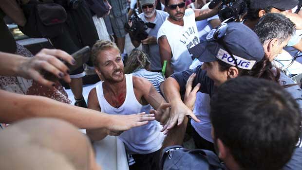Manifestante discute com policiais no protesto desta quarta-feira (7) em Tel Aviv (Foto: Reuters)