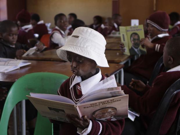 A pequena Ontlametse Phalatse, de 12 anos e portadora de progéria, lendo na sala de aula. (Foto: Denis Farrell / AP Photo)