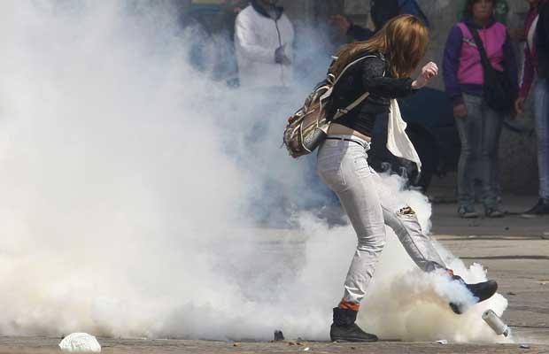 Manifestante chuta granada de gás durante protesto nesta quinta-feira (8) em Valparaiso (Foto: Reuters)