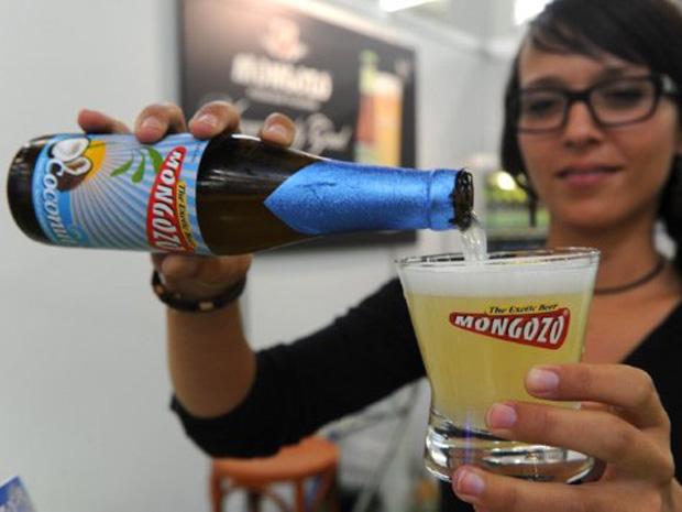 Expositora mostra cerveja sabor coco em feira de comércio sustentável na Alemanha (Foto: AFP)