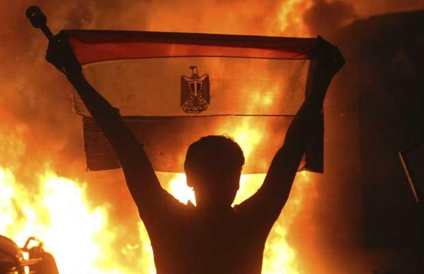 Manifestante ergue bandeira do Egito em frente a fogueira diante do prédio da Embaixada de Israel, nesta sexta-feira (9), no Cairo (Foto: AP)