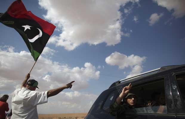 Moradores acenam bandeira líbia em posto de controle rebelde em Wish Tata, no caminho de Bani Walid, nesta sexta-feira (9) (Foto: AP)