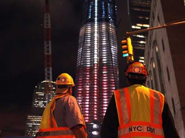 Trabalhadores observam as cores da bandeira dos Estados Unidos projetadas na Freedom Tower, que fica na região onde estavam as Torres Gêmeas, em Nova York. O país se prepara para o 10 º aniversário da tragédia provocada pelos ataques terroristas ao World  (Foto: Spencer Platt / Getty Images / AFP Photo)