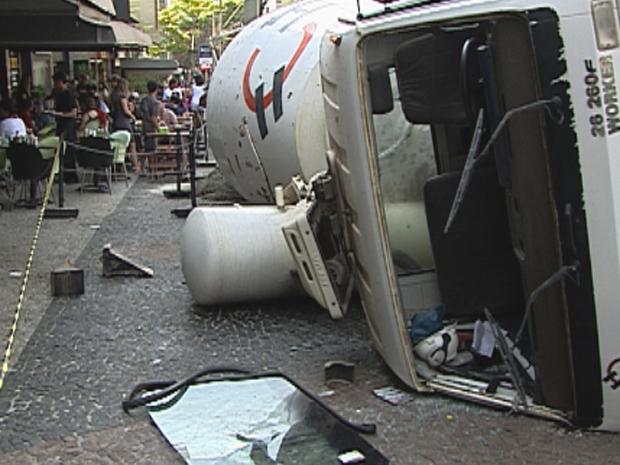 Um caminhão bateu em quatro carros, invadiu a calçada e quase atingiu um restaurante neste sábado (10) no bairro São Bento, na Região Centro-Sul de Belo Horizonte. De acordo com a polícia, o veículo desceu a rua desgovernado e só parou ao bater nos veículos. Um dos carros desapareceu debaixo do caminhão. Este veículo pertencia a uma mulher grávida que havia acabado de sair do carro quando aconteceu o acidente.  (Foto: Reprodução TV Globo)