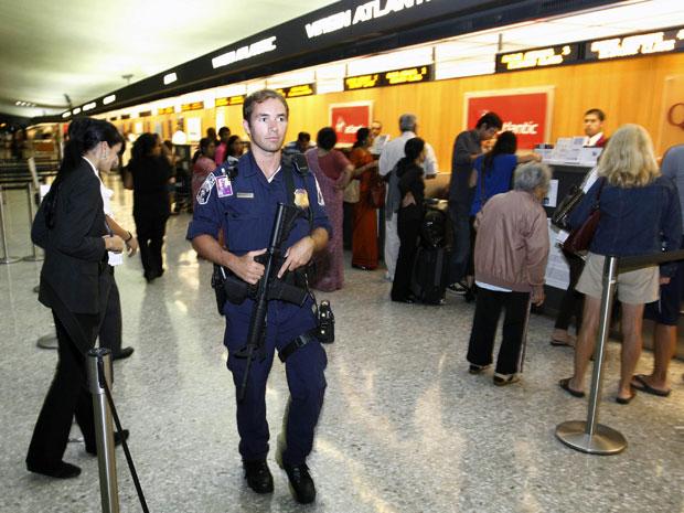 Oficial percorre o saguão do aeroporto Washington Dulles após pacote suspeito ser encontrado (Foto: Luis M. Alvarez/AP)