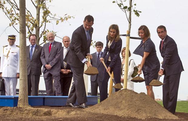 Príncipe Felipe (esquerda) e a princesa Letizia, ao seu lado, removem a terra onde plantaram uma árvore ao lado do embaixador americano em cerimônia que marca os 10 anos dos atentados de 11 de setembro, em Madri (Foto: Paul White/AP)