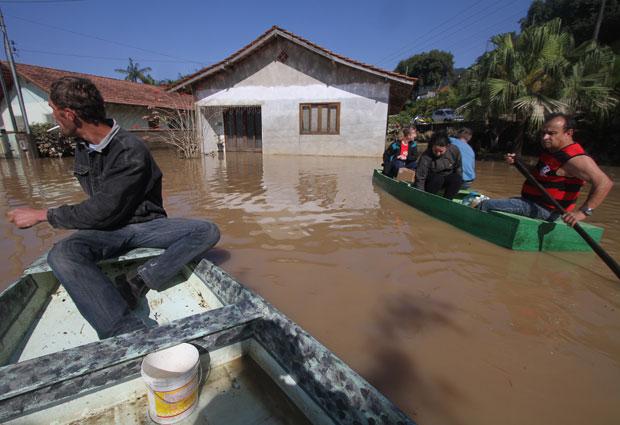 Moradores trabalham na limpeza e resgatam pertences de suas casas em região alagada pelas chuvas no bairro de Canoas, na cidade do Rio do Sul, em Santa Catarina, neste domingo (11) (Foto: Alexandro Auler/AE)