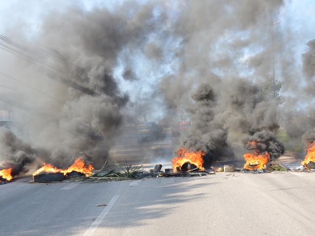 Manifestantes atearam fogo em pneus e colocaram pedras sobre a pista (Foto: Walter Paparazzo/G1)