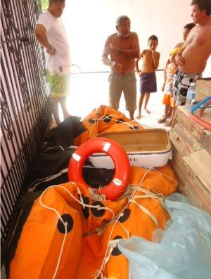 Januário (centro) e o bote que lhe garantiu sobrevivência (Foto: Mércia Souza/Colaboração)