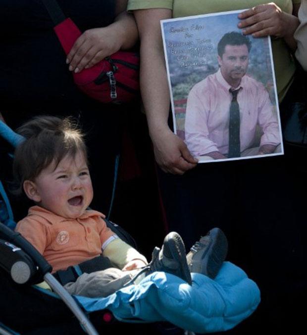 Criança chora ao lado de uma foto de Felipe Camiroaga (Foto: AFP)