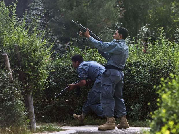 Policiais afegãos atiram contra o prédio em que os militantes talibãs se entrincheiraram nesta terça-feira (13) durante ataque em Cabul, capital do país (Foto: Reuters)