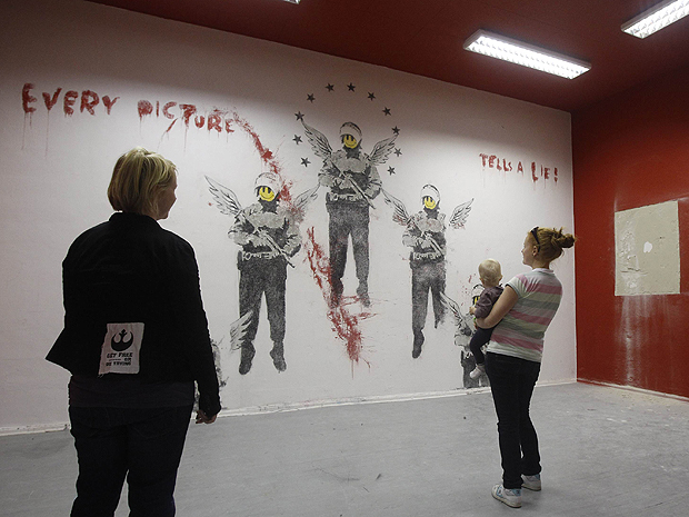 Mulher observa o painel de Banksy em Berlim (Foto: Reuters)