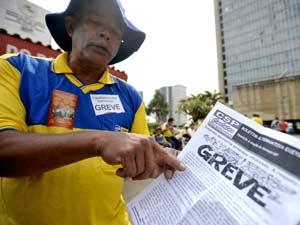 Funcionário dos Correios em Brasília, nesta quarta-feira, mostra jornal que trata da greve da categoria (Foto: Marcello Casal Jr./ABr)