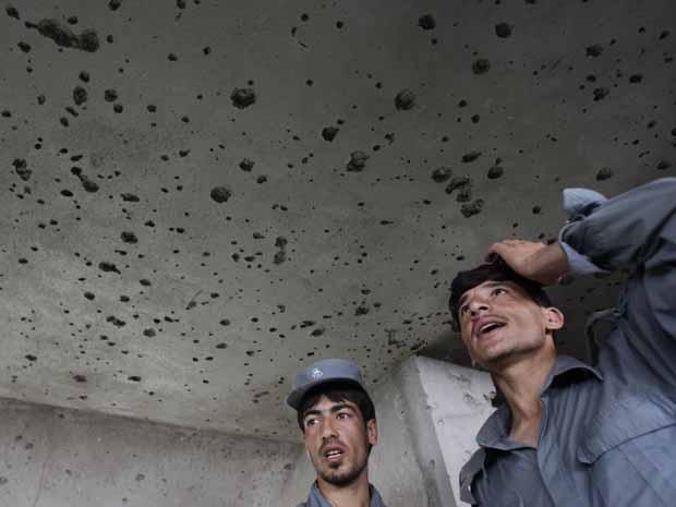 Policiais afegãos observam estragos no prédio ocupado pelos talibãs em Cabul, na manhã desta quarta-feira (14) (Foto: AP)