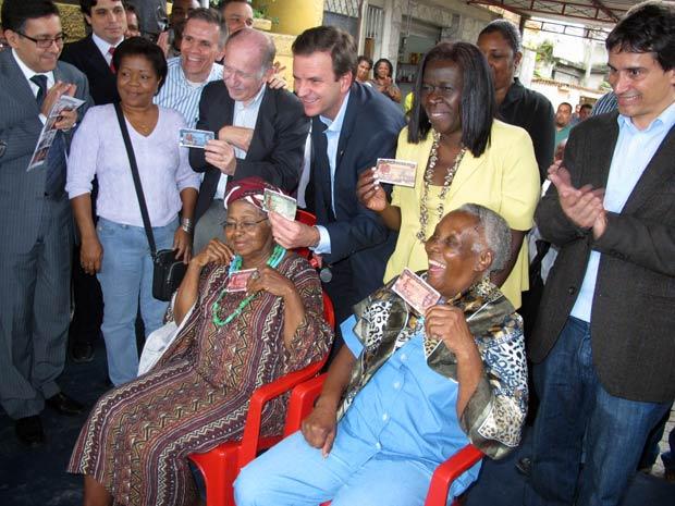 Moradoras há muitos anos da Cidade de Deus, D. Benta e D. Geralda (sentadas) estampam as cédulas de CDD.  (Foto: Bernardo Tabak/G1)