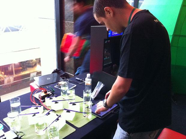 Luis Queiroz demonstra o seu 'Caipirinha Hero', jogo em que é possível criar músicas a partir de leves batidas em copos –na demonstração feita no Google Developer Day, ele substituiu a capirinha, por água. No jogo, o usuário pode selecionar quais notas quer que o game execute sobre os copos (Foto: Amanda Demetrio/G1)