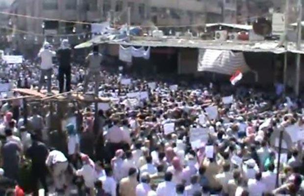 Manifestantes protestam contra o governo em Houma, subúrbio de Damasco, nesta sexta-feira (16), em imagens divulgadas pelo YouTube (Foto: AP)