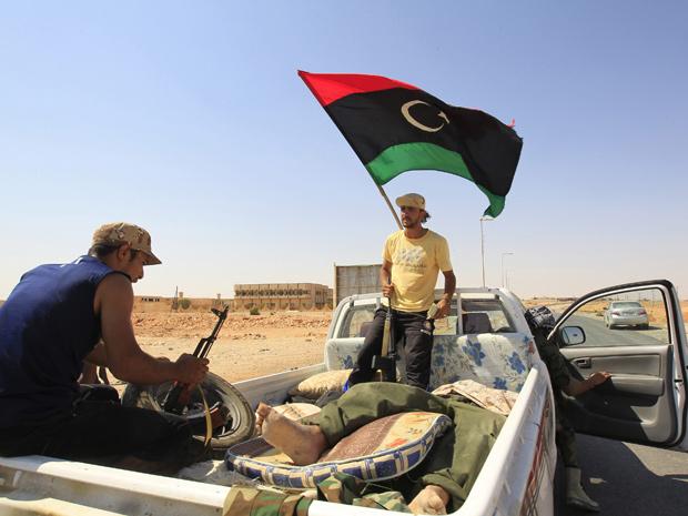 Soldados a serviço do Conselho Nacional de Transição carregam corpo de inimigo morto no cerco a Bani Walid (Foto: Reuters / Zohra Bensemra)