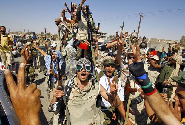 Rebeldes líbios comemoram a tomada de controle de mais uma vila pró-Kadhafi, em Gohta, neste domingo (18) (Foto: Francois Mori/AP)