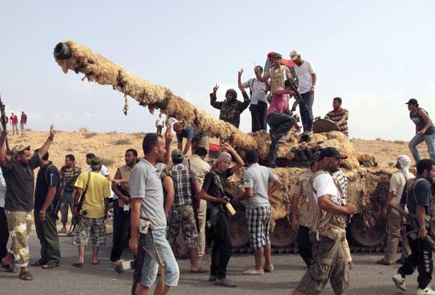 Combatentes leais ao novo governo da Líbia celebram a captura de tanque das forças pró-Kadhafi, próximo a Sirte, cidade-natal do coronel, nesta terça-feira (20) (Foto: AP)