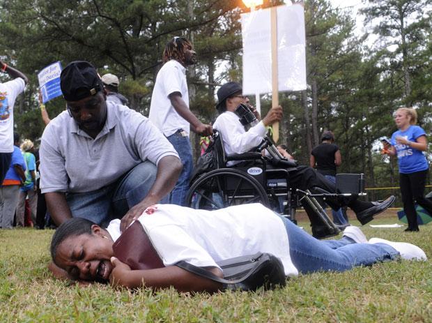 Mulher chora no chão comemorando após saber do adiamento da execução de Davis nesta quarta (21), em frente ao presídio de Jackson (Foto: Tami Chappell/Reuters)