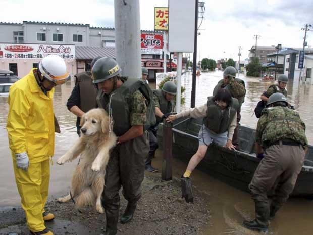 Soldados resgatam um cão e uma mulher em uma vila inundada após passagem do tufão 'Roke' em Koriyama. (Foto: Reuters)