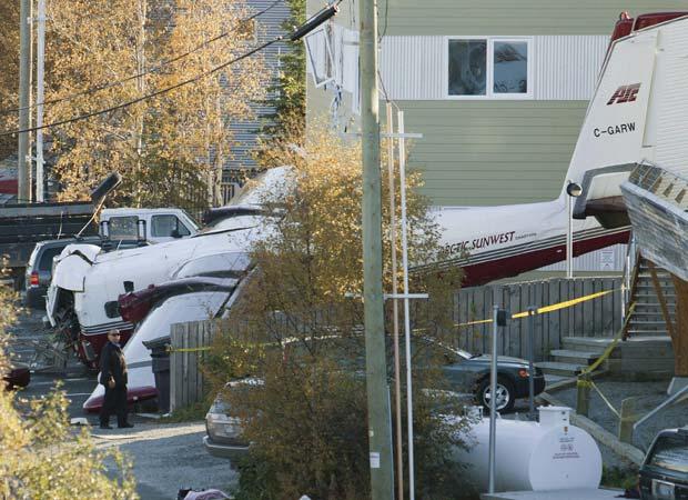 Destroços de pequeno avião que caiu nesta quinta-feira (22) em conjunto residencial em Yellowknife, no Território do Noroeste, no Canadá. Duas pessoas morreram e sete ficaram feridas, todas elas a bordo do avião. Na queda, um carro foi destruído, segundo testemunhas (Foto: AP)